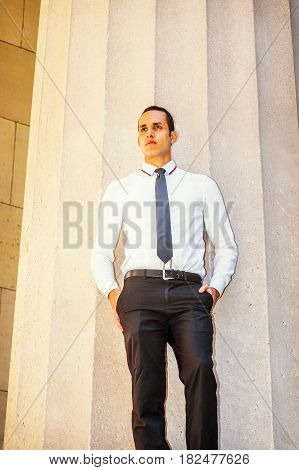 Young American Businessman wearing white shirt black tie hands in pockets standing outside office building in New York thinking lost in thought.
