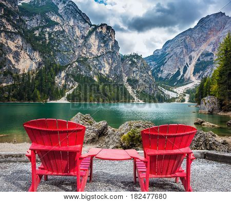 The concept of walking and eco-tourism. Two red deck chairs on the shore of the lake. Water reflects the surrounding mountains