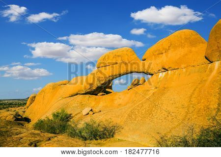 Mountain Nature Reserve in the desert. Stone arch Spitzkoppe, Namibia. The concept of extreme and ecological tourism