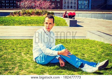 Young American Man wearing white shirt blue pants white sneakers sitting on green lawn at park in New York thinking. Woman with children strollers on background. Concept of missing family friend.