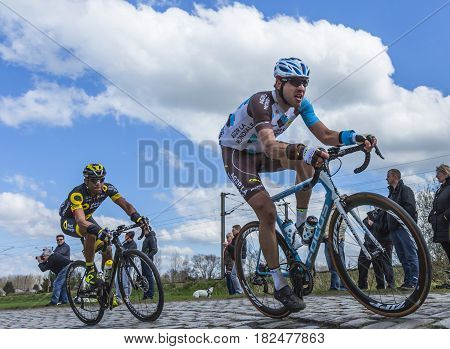 Hornaing France - April 102016: Two cyclists Gediminas Bagdonas of AG2R La Mondiale and Yohann Gene of Direct Energie riding in the peloton on a paved road in Hornaing France during Paris Roubaix on 10 April 2016.