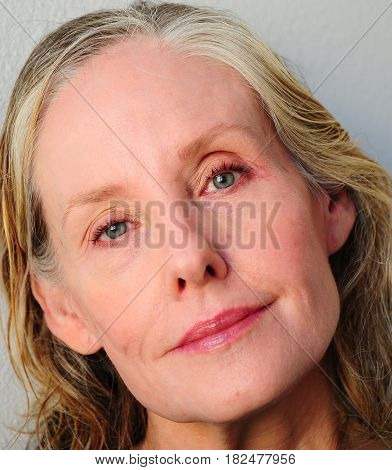 Mature female blond beauty expressions indoors alone.