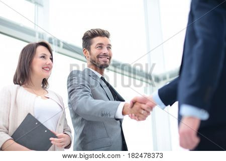 Two business people shaking hands and looking at each other with