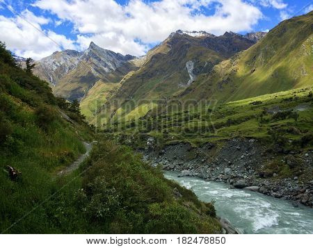 Glacial river flowing through rugged, green mountain valley with sunny blue skies.