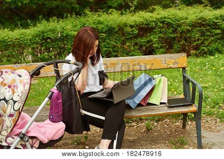 A woman with baby carriage and shopping bags is speaking on the phone and working with tablett in the park, while sitting on a bench.