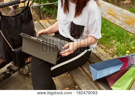 Crop shot of a woman with baby carriage and shopping bags working with tablett in the park while sitting on a bench.