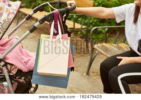 Crop shot of a woman holding with one hand a baby carriage while sitting on a bench.
