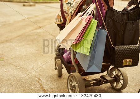 Outdoor crop shot of baby carriage with shopping bags. Copy space.