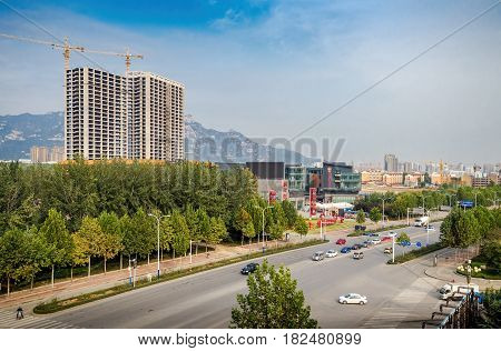 Tianjin, China - Nov 1, 2016: Small town scene just outside Tianjin City. Captured from within a High-Speed Rail (HSR), showing wide roads and some commercial activities.