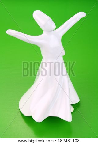 Whirling derwish on green background close up image