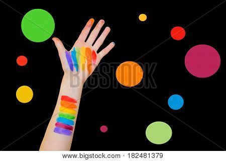 A girls' outstretched arm and palm painted with a rainbow of colors against a solid color background and colourful polka dots