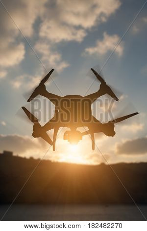 Silhouette of Unmanned Aircraft System (UAV) Quadcopter Drone In The Air At Sunrise.