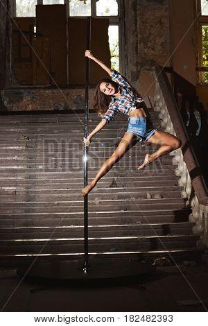 Beautiful brunette dancing on a pole