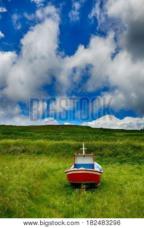 Spanish destination, Galicia, little boat on a green meadov, retirement concept image