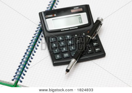 Calculator And Pen On The Checkered Book