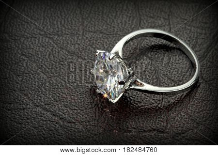 Diamond solitaire ring on black leather background