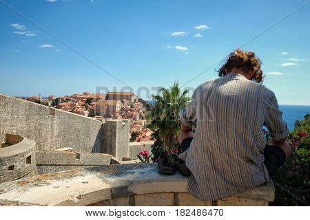 young tourist resting sitting on a wall in front Dubrovnik Old Town