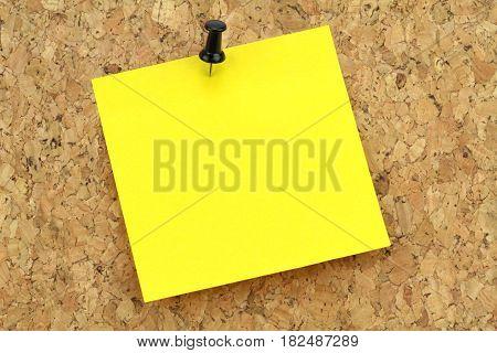 Yellow note paper on cork board Macro image
