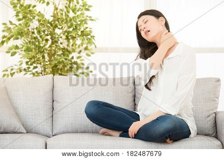 Woman Sitting On Sofa With Neck Pain