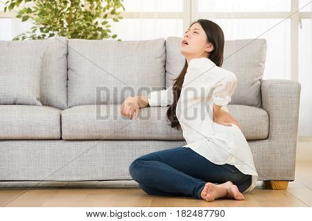 Woman Sitting On Floor Touching Her Back
