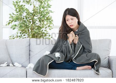 Woman Feeling Cold Sitting On Sofa