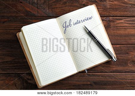 Text JOB INTERVIEW written in notebook on wooden background. Human resources concept