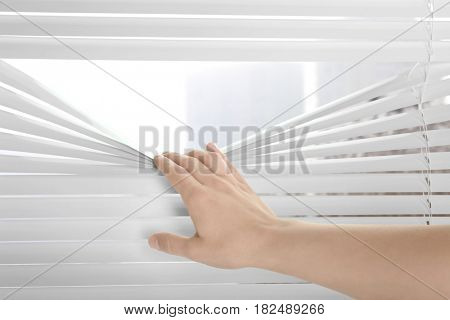 Woman separating slats of blinds and looking through window
