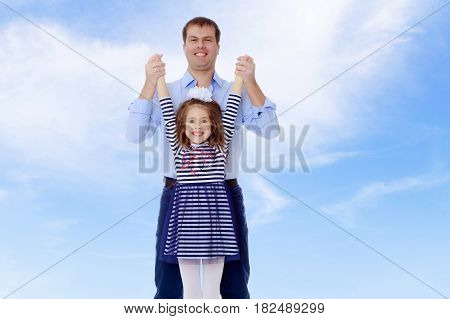 Happy young dad raise his beloved daughter's hands.On the background of summer blue sky and fluffy clouds.