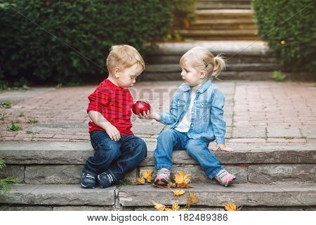 Group portrait of two white Caucasian cute adorable funny children toddlers sitting together sharing apple food love friendship childhood concept best friends forever