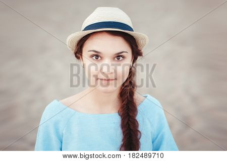 Closeup portrait of beautiful pensive white Caucasian brunette girl with brown eyes and plait in blue dress and straw hat looking in camera rustic retro vintage style concept