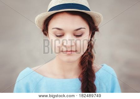 Closeup portrait of beautiful pensive white Caucasian brunette girl with plait in blue dress and straw hat looking down rustic retro vintage style concept