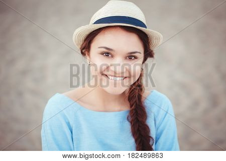 Closeup portrait of beautiful smiling white Caucasian brunette girl with brown eyes and plait in blue dress and straw hat looking in camera rustic retro vintage style concept