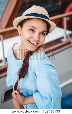 Portrait of beautiful smiling white Caucasian brunette girl on boat yacht pier quay in blue dress and straw hat posing making funny emotional faces expressions having fun