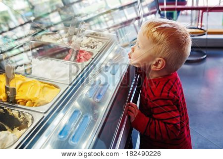 Portrait of cute adorable white Caucasian funny blond child boy looking at ice cream in shop window trying to choose one looking surprised puzzled emotional face expression