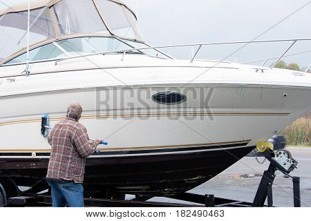 Caucasian man cleaning boat hull with brush