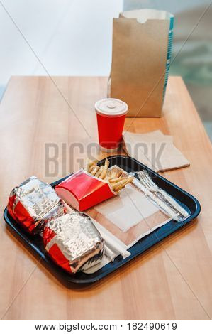 Closeup shot image of two burgers wrapped in tinfoil french fries potato chips red cup of coffee or tea on tray on wooden table in fast food restaurant