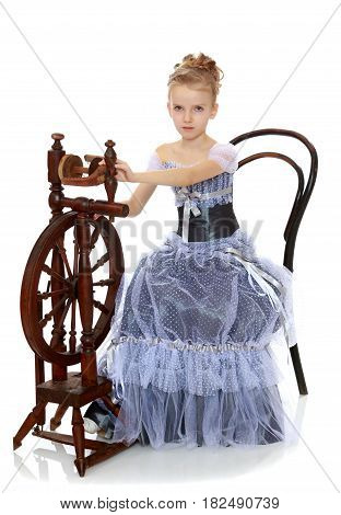 Beautiful little blonde girl dressed in a Princess dress. Girl sitting at the old spinning wheel and shows the yarn manufacturing process.Isolated on white background.