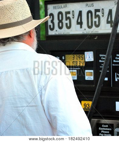 Male senior at the gas pump looking at the high prices.