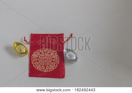 Gold and silver ingot Red bag for Chinese New Year on white background Translation in English meaning lucky and richly