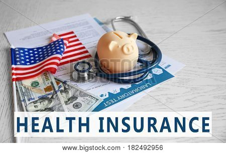Text HEALTH INSURANCE, money, stethoscope and USA flag on wooden background