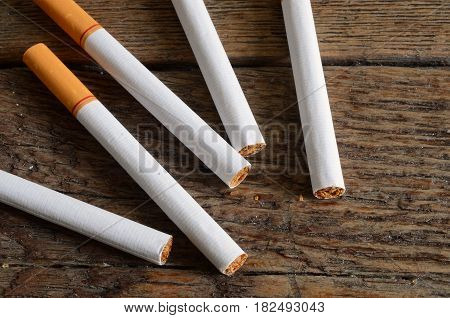 A top view image of several loose cigarettes on a wooden table.