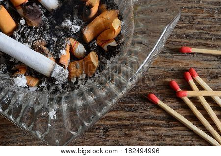 A close up image of a dirty ashtray and several wooden match sticks.