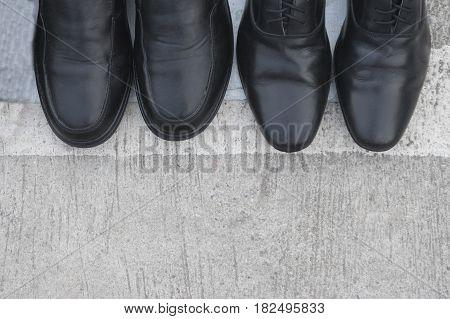 Black patent leather men shoes against concrete background