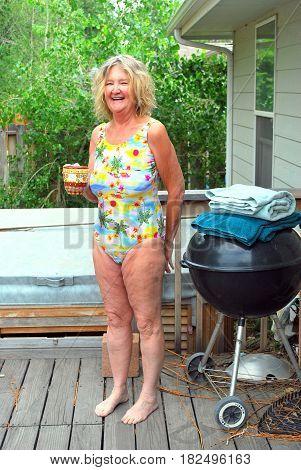 Mature female senior blond beauty enjoying her hot tub at home.