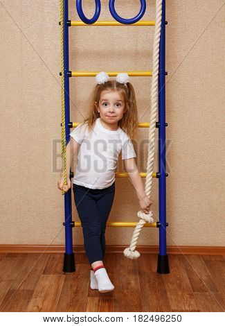Little girl in sportswear holding a rope. The concept of a healthy lifestyle from a young age. Children's sports.