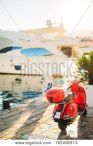 A red retro moped parked at the marina. In Budva, Montenegro