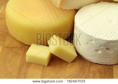 Various cheeses on wood background close up image