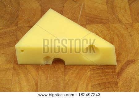 Emmental cheese on wood background close up image