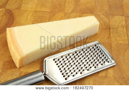 Parmesan cheese and grater on kitchen board
