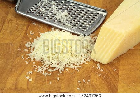 Parmesan cheese and grater close up image